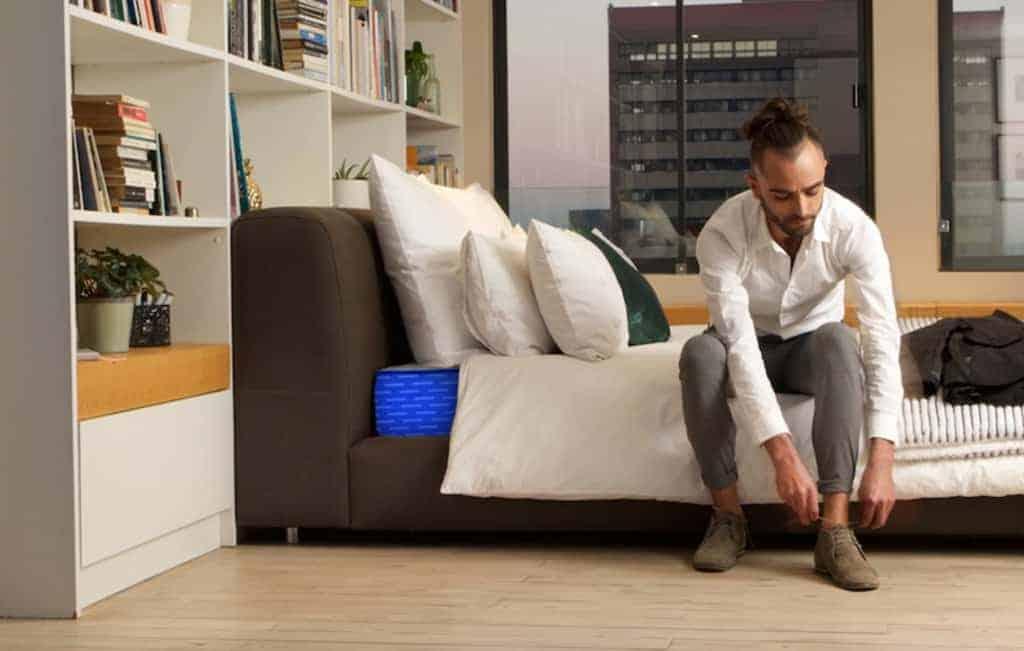 Man sits on genie mattresses bed