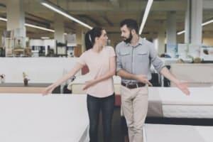 Couple in bed store choosing between a memory foam mattress, latex mattress or an orthopaedic mattress