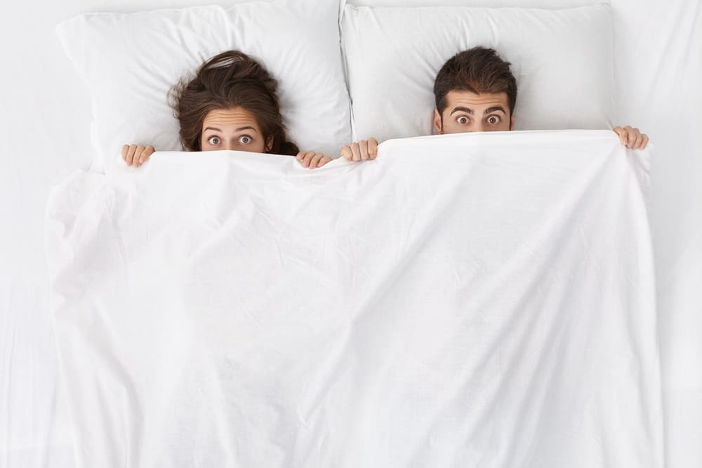 Couple laying shocked in bed